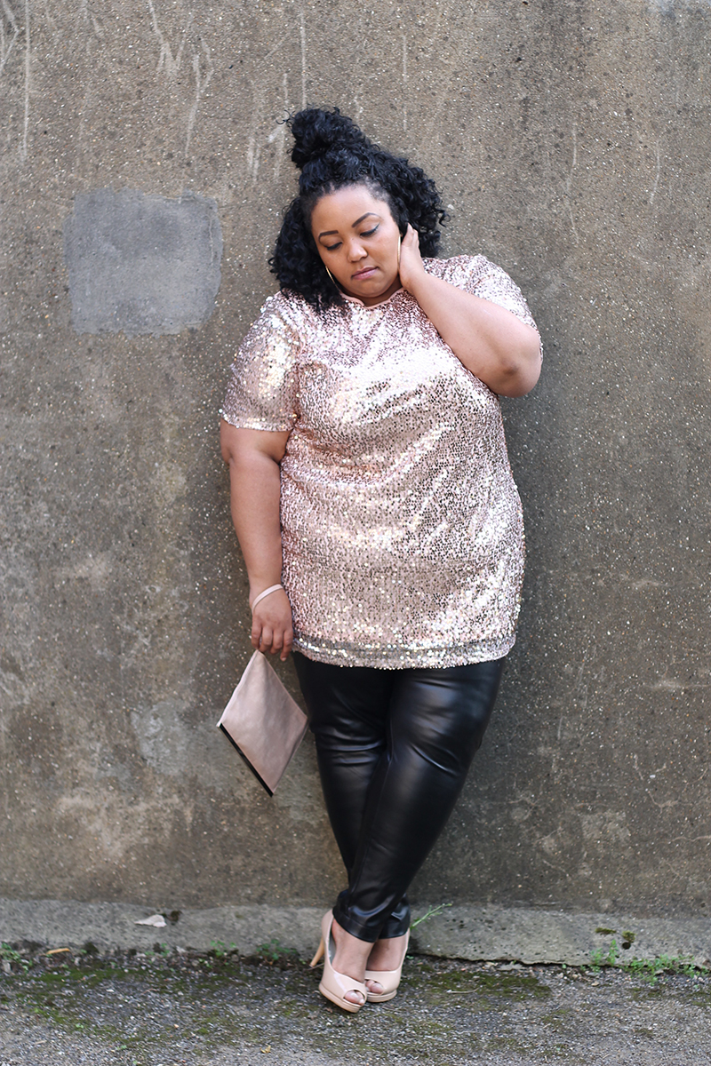 A plus size woman wearing a pink sequin dress, wet look leggings and open toe nude heels