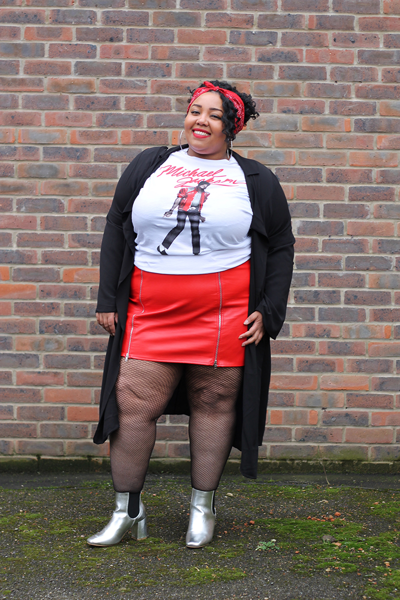 A plus size woman smiling wearing a Michael Jackson beat it t-shirt, red faux leather zip front mini skirt, black duster jacket, silver metallic Chelsea boots and red bandana