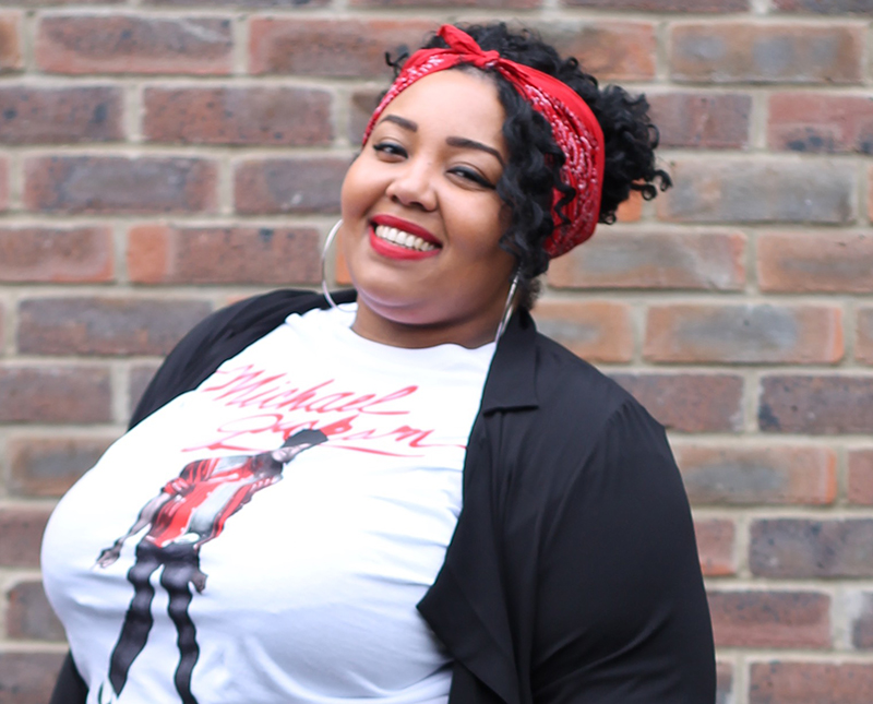 A plus size woman smiling wearing a Michael Jackson beat it t-shirt and red bandana