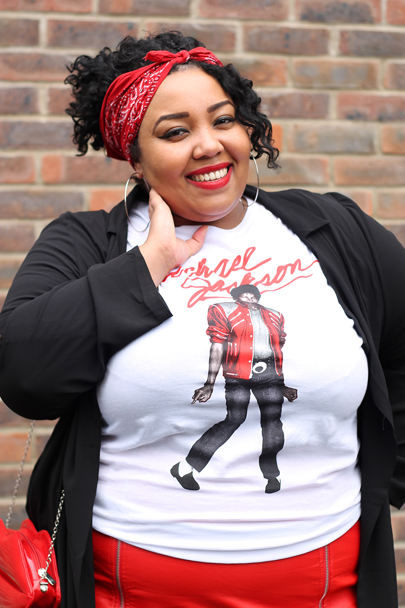 A plus size woman smiling wearing a Michael Jackson beat it t-shirt, red faux leather zip front mini skirt, black duster jacket, red bandana and red lips bag