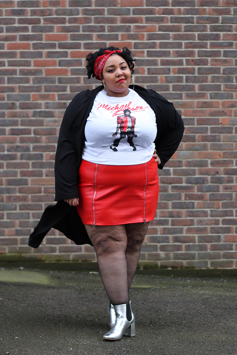 A plus size woman wearing a Michael Jackson beat it t-shirt, red faux leather zip front mini skirt, black duster jacket, silver metallic Chelsea boots and red bandana