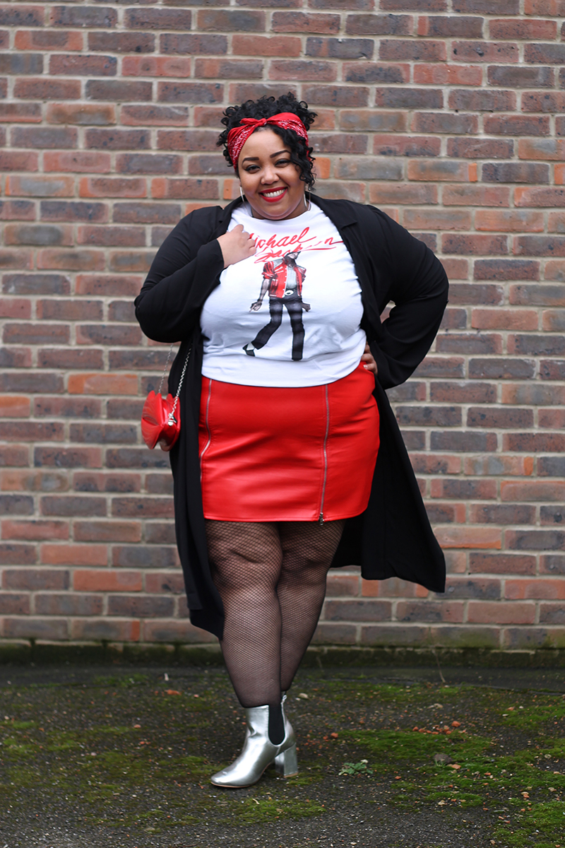 A plus size woman smiling wearing a Michael Jackson beat it t-shirt, red faux leather zip front mini skirt, black duster jacket, silver metallic Chelsea boots, red bandana and red lips bag