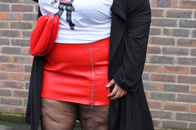 A plus size woman wearing a Michael Jackson beat it t-shirt, red faux leather zip front mini skirt, and black duster jacket