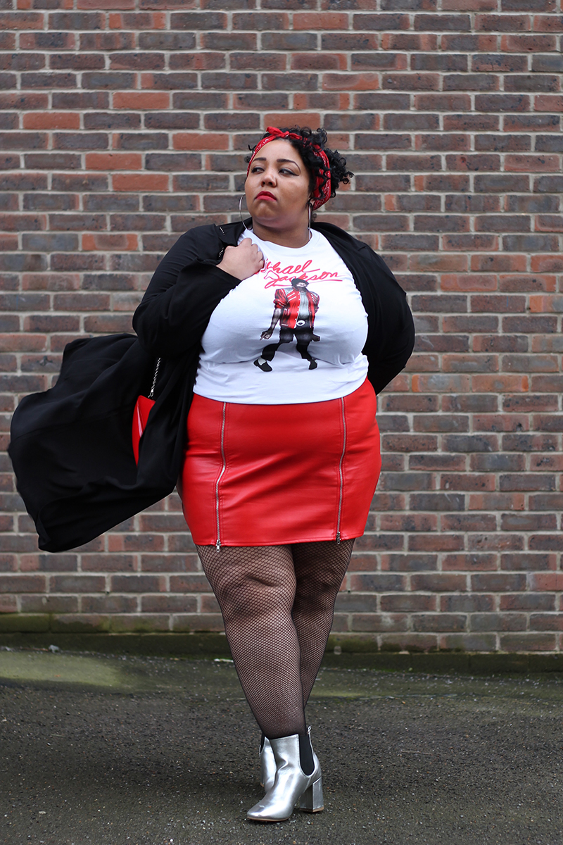 A plus size woman wearing a Michael Jackson beat it t-shirt, red faux leather zip front mini skirt, black duster jacket, silver metallic Chelsea boots, red bandana and red lips bag