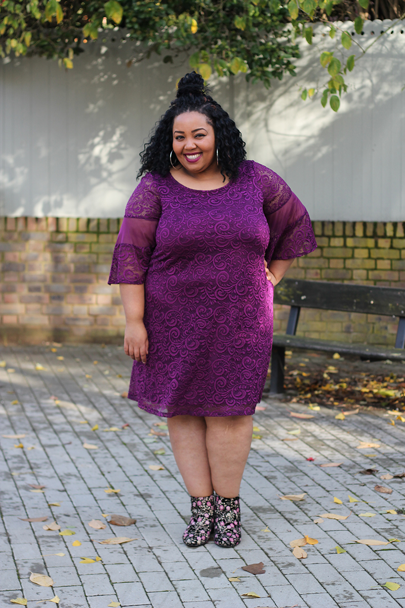 Plus Size woman smiling wearing purple Bell-Sleeve Lace & Mesh Swing Dress and floral ankle boots