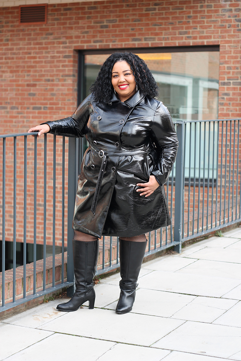 Plus Size woman smiling wearing a black faux leather trench coat and leather boots