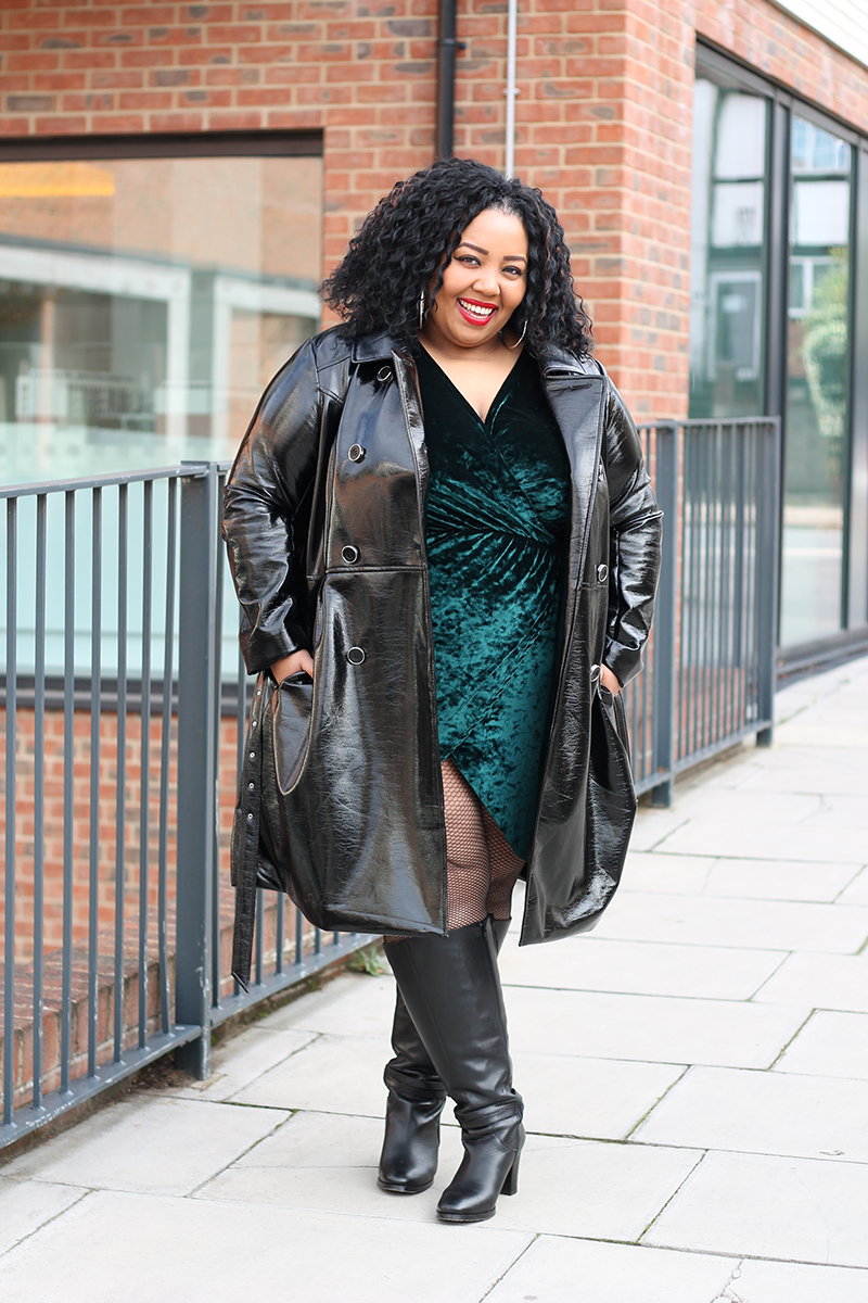 Plus Size woman smiling wearing a black faux leather trench coat, leather boots and velvet dress