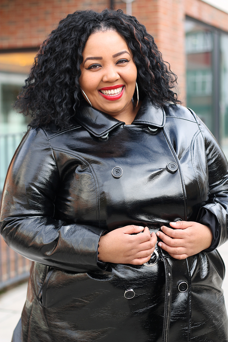 Plus Size woman smiling wearing a black faux leather trench coat