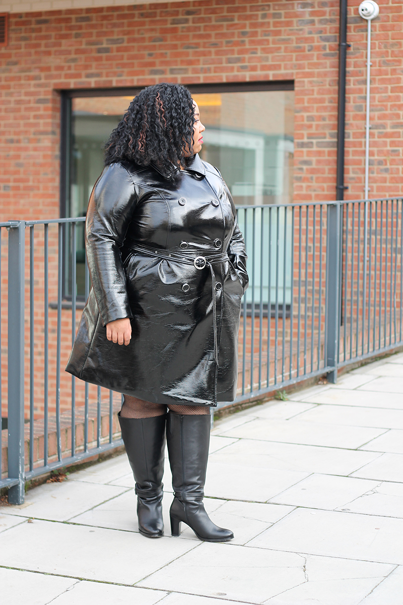Plus Size woman wearing a black faux leather trench coat and leather boots