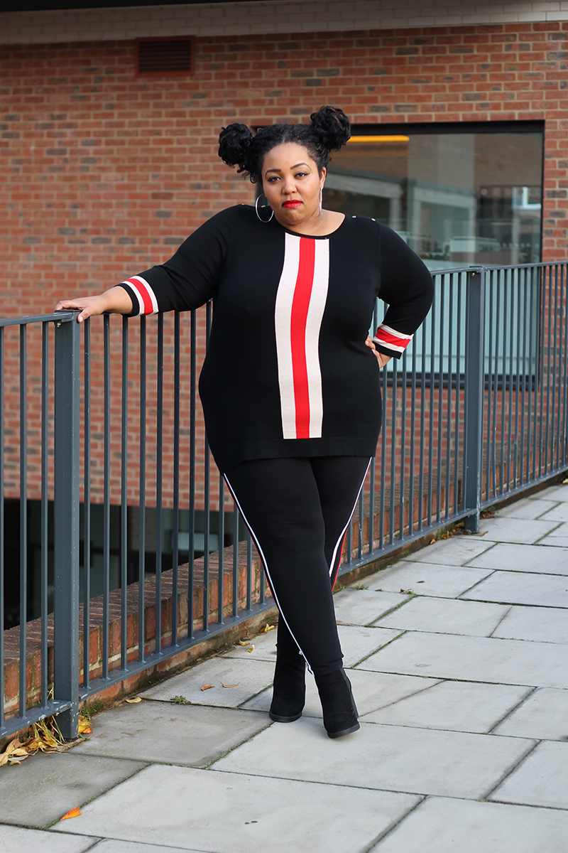 Plus Size woman wearing black side striped leggings and a black vertical stripe sweater and ankle boots